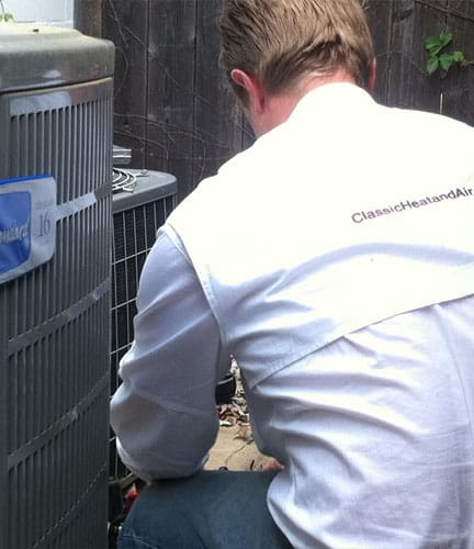 Classic Heating & Air employee looking at air conditioning unit