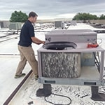 employee performing maintenance on commercial HVAC system