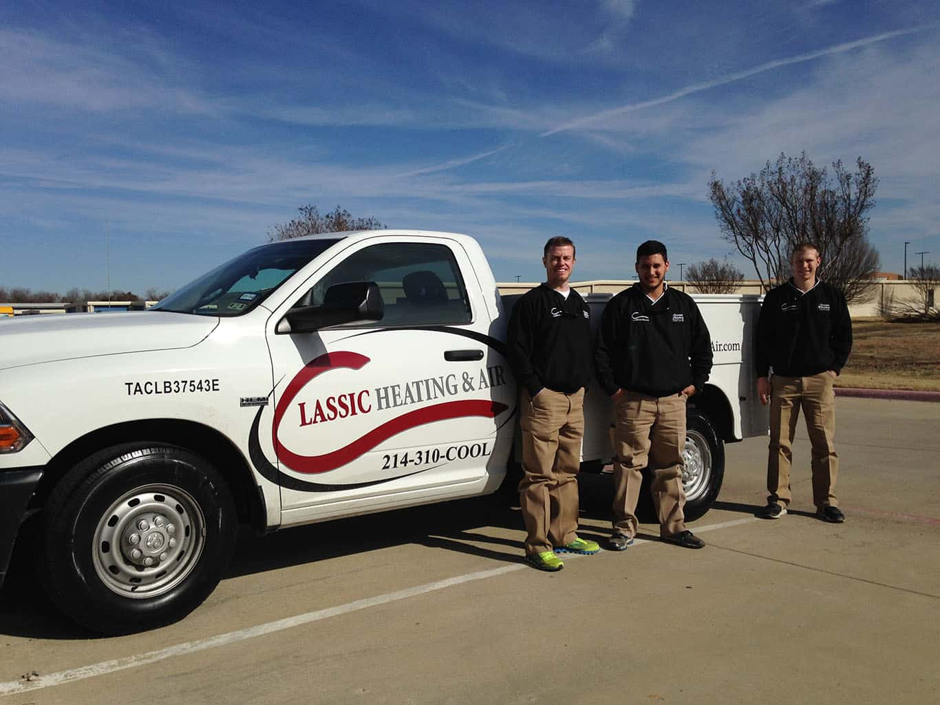 3 men in Classic Heating & Air uniform posing next to Classic Heating & Air pickup truck